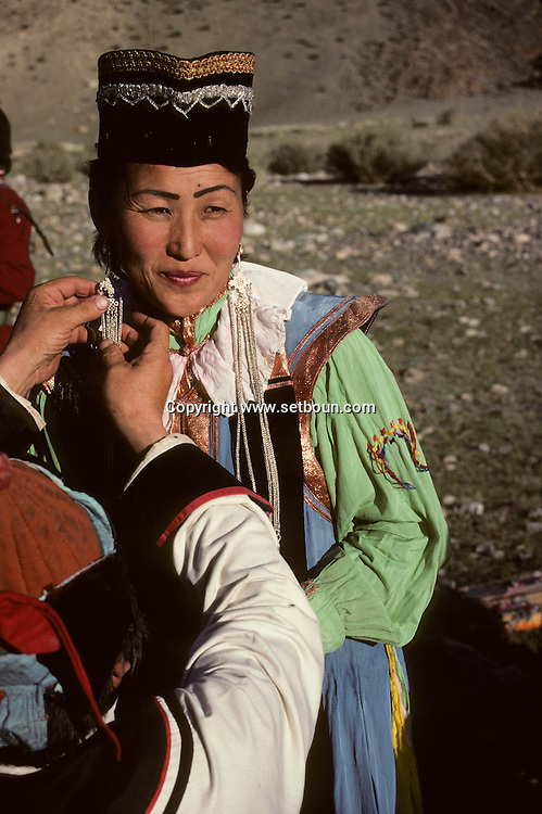 Mongolia. Getting ready for a concert. In the improvised wings of an open air  - theatre - , a singer dressed in the traditional Zaqtchin Mongol dress is assisted as she dons her long silver earrings before going on stage (Manqan, in the aymag of Qovd). In the Altay mountain region in western Monglia, many small Mongolian ethnic groups live side by side.  The Zaqtchins, with their curious traditional dress, are one of them.  This outfit - reserved for important occasions - can also be used as stage dress for the local artists.   / Préparation au concert. (Sum de Mangan, dans aymag de Qovd, Mongolie). Dans une sorte de coulisses improvisées en plein air cette chanteuse, revêtue d'un costume traditionnel typique des Mongols zaqtchin, se fait aider à mettre ses longues boucles d'oreille en argent ciselé, avant d'entrer en scène. ( Chanteuse en costume zaqtchin. Dans la région de la chaîne de l'Altay à l'ouest de la Mongolie, une mosaïque de petites ethnies mongoles coexistent, dont les zaqtchin au costume singulier. Porté uniquement aux grandes occasions de fête, cet ensemble peut aussi servir de tenue de scène pour les artistes originaires de l'endroit.