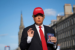Edinburgh, Scotland, UK. 15 August 2019. Warm sunny weather in Edinburgh brought thousands of tourists onto the Royal Mile to enjoy the many street performers and actors promoting their shows during the Edinburgh Festival Fringe. Donald Trump makes an appearance promoting show Trumps' Fake TV.  Iain Masterton/Alamy Live News ++ Editorial Use Only ++