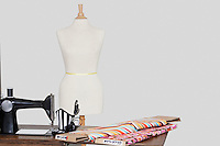 Tailor's dummy with hat and cloth pattern on sewing machine over colored background