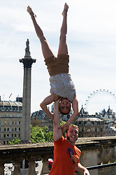 © Licensed to London News Pictures. 22/05/2017. London, UK. Members of the Canadian circus troupe Flip FabriQue perform on the roof of Canada House overlooking Trafalgar Square in London.  The circus makes its London premiere this Summer with Catch Me production at the Underbelly festival. Photo credit: Ray Tang/LNP