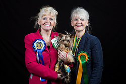 © Licensed to London News Pictures. 10/03/2016. Birmingham, UK. Identical twins Brenda Haslan (left) and Margaret Evans with their Yorkshire Terrier named Kit at Crufts 2016 held at the NEC in Birmingham, West Midlands, UK. The world's largest dog show, Crufts is this year celebrating it's 125th anniversary. The annual event is organised and hosted by the Kennel Club and has been running since 1891. Photo credit : Ian Hinchliffe/LNP