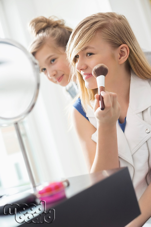 Girl watching sister applying makeup in front of mirror at home