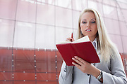 Beautiful businesswoman reading notes in organizer while standing against office building