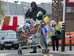 © Licensed to London News Pictures. 30/03/2020. London, UK. A man wearing a mask places shopping back in to an overflowing shopping trolley outside Sainsbury's supermarket at Ladbroke Grove in west London. Members of the public have been told they can only leave their homes when absolutely essential, in an attempt to fight the spread of COVID-19, . Photo credit: Ben Cawthra/LNP