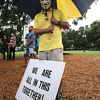 People gather in the rain at Lake Eola park during the Orlando Is Ferguson event in downtown Orlando, Florida on Saturday, August 16, 2014. In light of the recent killing of eighteen year old Mike Brown in Ferguson, Missouri, and the aftermath, citizens are uniting to discuss possible solutions to law enforcement reform and other options for safer police and citizen encounters.  (AP Photo/Alex Menendez)