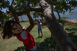 Syria.<br /> Girls playing with a 'Marioneta in spanish' in front of a small lake in the town  of Al-Qala a small town with an ancient castle occupied by the Syrian regime in Hama province, Syria,<br /> 15th June 2013<br /> Picture by Daniel Leal-Olivas / i-Images
