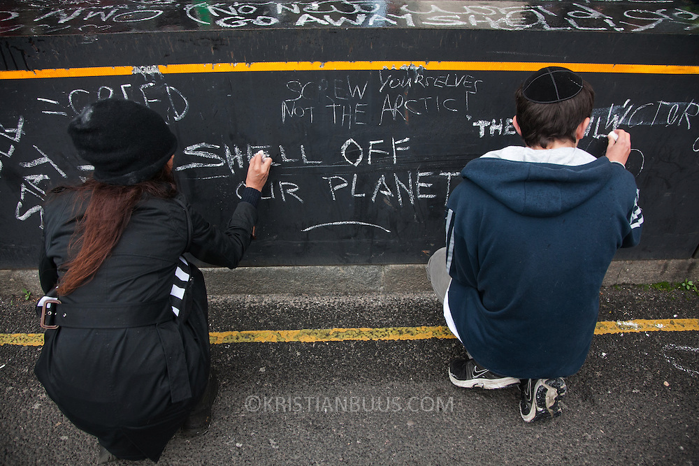 Comments to Shell written in chalk on the security fence outside Shell's London HQ. The giant polar bear puppet Aurora made by Greenpeace walked the streets of London in defence of the Arctic as part of a Greenpeace global day of action. The parade,part performance part protest, was to highlight the melting ice caps and the increasing and potentially devastating oil drilling in the arctic sea. Shell is one of the companies drilling and the march through London ended up outside Shell London HQ to draw attention to their oil business in the arctic. Aurora, the biggest polar bear in the world represents all endangered species in arctic.