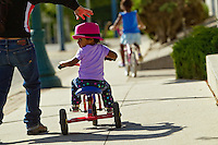 Celeste Harris, 2, tries to catch a peek at what's behind her as she pedals her tricycle while her mother Nidia Harris attempts to correct her Thursday as they head toward City Park in Coeur d'Alene.