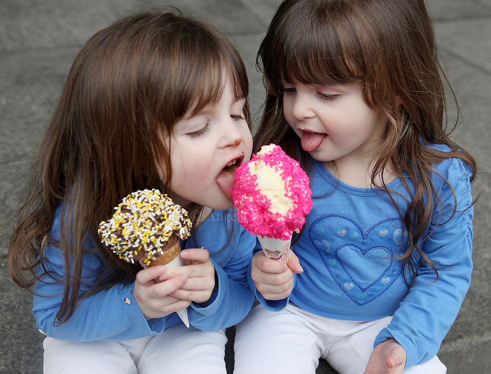 Olivia Cardenas, 3, left, takes a lick from twin sister Emerson's ice cream at Faneuil Hall Market in Boston, Monday,  February 14, 2011.
