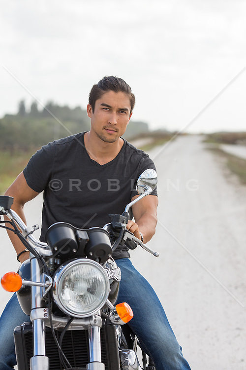 rugged Asian American man on a  motorcycle