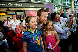 © Licensed to London News Pictures. 23/08/2016. London, UK. Matt Langridge,, Olympic gold medalist in the mens rowing eight, poses for members of the public with his gold medal as the team arrives at terminal 5 of London Heathrow Airport . Team GB finished second in the medals table with 67 medals, beating their total of 65 at London 202.  Photo credit: Ben Cawthra/LNP