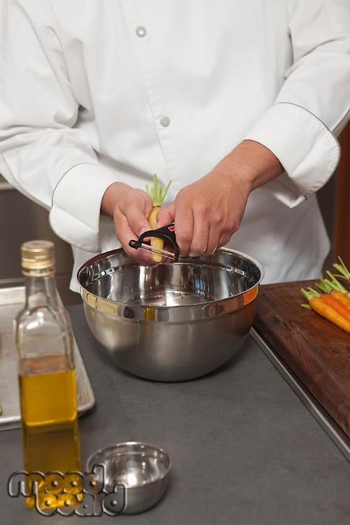 Mid- adult chef peeling carrots