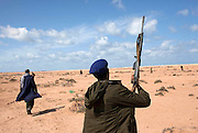 Frontline Libyan rebel fighters advance during a battle with pro-Qaddafi forces just outside the coastal town of Bin Jawwad. Rebels fought pro-Qaddafi forces there throughout the day as they tried to regain control the town from government forces that seized the town overnight.