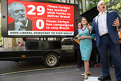 London, UK. 14 May, 2019.  Jo Swinson MP, Deputy Leader, and Ed Davey, MP for Kingston and Surbiton, launch a poster criticising Labour Party Leader Jeremy Corbyn's cooperation with the Conservative Party in attempting to deliver Brexit to be used as part of the Liberal Democrats' European election campaign.