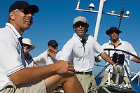 Sailors relaxing on yacht by helm