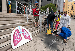 """© Licensed to London News Pictures;27/06/2020; Bristol, UK. Protesters clean up the soot they had dumped as a protest but leave a chalk message on the pavement as Extinction Rebellion end a week of protests by dumping soot from a giant pair of lungs onto the steps of the headquarters of the West of England Combined Authority (WECA) as the over-arching regional authority in the area. Extinction Rebellion's Five a Week campaign for clean air is highlighting the number of premature deaths in Bristol due to air pollution. They set up 296 pairs of shoes on College Green in front of City Hall with the message """"296 Deaths a Year"""" which the campaigners say is the number of people who die each year due to air pollution in the city. On Thursday five Extinction Rebellion activists climbed up the central dome of Bristol City Hall and say they will stay up there until Bristol City Council commits to ensuring legally clean air in every suburb of the city by April 2021. Extinction Rebellion demand urgent action from Bristol City Council & WECA (West of England Combined Authority) to protect people's lungs and protect the planet, saying health is intrinsically linked to the health of the environment. XR want Clean Air Equality for Life, not just for the coronavirus Covid-19 lockdown, saying there is a unique opportunity as we come out of lockdown to envision a Bristol that puts people's health and the health of the planet first, and put pressure on elected officials to help build the city back better. Photo credit: Simon Chapman/LNP."""