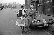 Teddy boy couple stood in front of Pontiac Trans Am, 1980s.