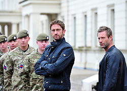 © Licensed to London News Pictures. 04/04/2013. London, UK Hollywood actors Gerard Butler and Aaron Eckhart with soldiers from F Company the Scots Guards.  Butler met the soldiers at Wellington Barracks in Central London ahead of a special preview screening of Hollywood movie Olympus Has Fallen, released 17th April 2013. ..The actors spent time talking to the soldiers prior to the troops watching a special preview of the film in the barracks.  Photo credit : Alison Baskerville/LNP