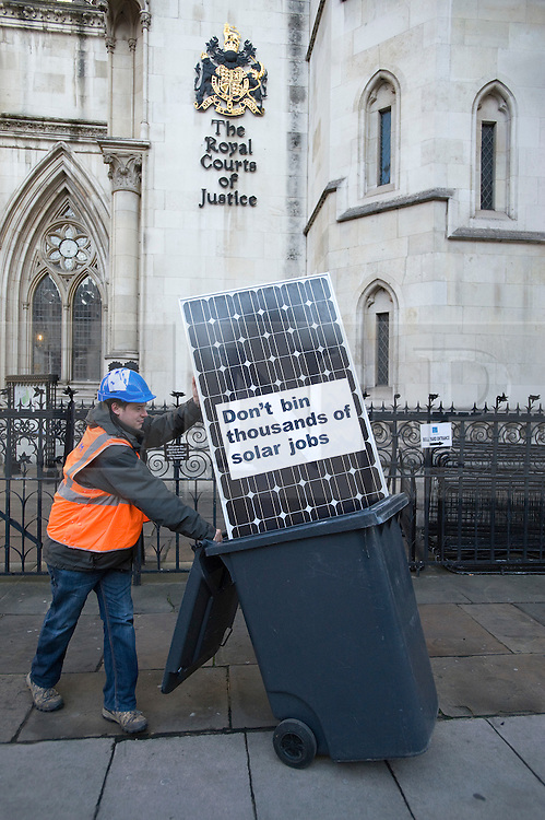 © Licensed to London News Pictures. 15/12/2011. London, UK.  Members of Friends of the Earth place a solar panel in a bin outside The High Court today (15/12/2011) where an application is being made to challenge the Governments plans to slash financial incentives for solar electricity. Photo credit: Ben Cawthra/LNP