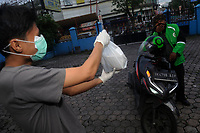 Medan, Indonesia, March 28, 2020: The daily life of a resident, Agus Zilnal (29) seen used the body protection during received food packaging through an online system to avoid the spread of Corona Virus Disease 19 transmitted in Medan, North Sumatra province, Indonesia on March 28, 2020.