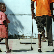 Kuito, Angola                                           September, 2002<br /> <br /> A seven-year-girl learns to walk on her new prosthetic leg. She lost her leg when she was five after she was shot while her mother was carrying her on her back.  Her mother was collecting  firewood. Photo by Lori Waselchuk/South Photographs