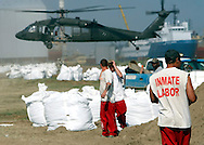 Inmates from a La Fourche parish jail on a work release program fill giant sandbags in Port Fourchon, Louisiana May 11, 2010. U.S. Army National Guard troops were dropping the sandbags with helicopters (background) on nearby breaks in beaches to protect marshes from the BP oil spill offshore.   REUTERS/Rick Wilking (UNITED STATES)