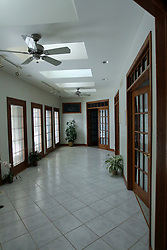 A solarium or atrium in a modern home has a tile floor, lots of 15 pane glass windows and doors, skylights and dual ceiling fans