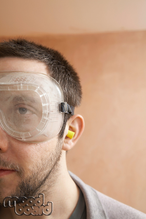 Man wearing protective eye goggles and earplugs indoor close up