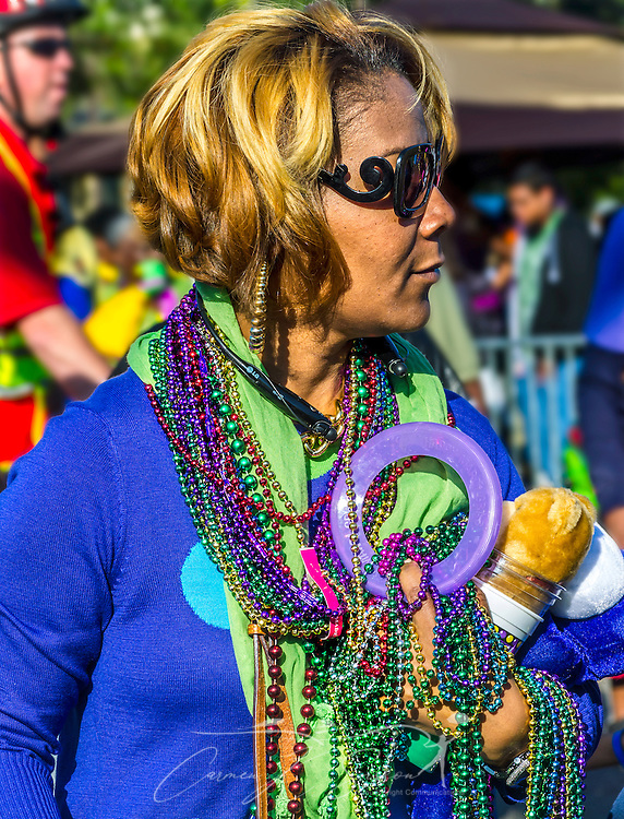 A parade goer carries loot she gathered during the Joe Cain Procession at Mardi Gras, March 2, 2014 in Mobile, Ala. French settlers held the first Mardi Gras in 1703, making Mobile's celebration the oldest Mardi Gras in the United States. (Photo by Carmen K. Sisson/Cloudybright)