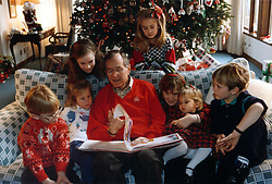 Camp David, Maryland - December 24, 1991 -- United States President George H.W. Bush reads a Christmas story to his grandchildren, Pierce Bush, Marshall Bush, Barbara Bush (daughter of George W. Bush), Lauren Bush, Jenna Bush (daughter of George W. Bush), Ashley Bush and Sam LeBlonde at Camp David in Maryland on Christmas Eve, December 24, 1991. Photo by White House via CNP/ABACAPRESS.COM