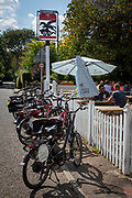 A row of electric bikes parked up outside the The Flying Horse Pub, Cage Land, Smarden, Kent, England, UK.  People sit and stand around a table outside the pub. (photo by Andrew Aitchison / In pictures via Getty Images)