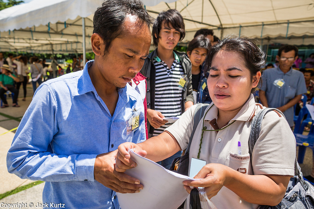 "17 JULY 2014 - BANGKOK, THAILAND:  A Thai immigration worker (right) helps an undocumented Cambodian man apply for a work permit at the temporary ""one stop service center"" in the Bangkok Youth Center in central Bangkok. Thai immigration officials have opened several temporary ""one stop service centers"" in Bangkok to register undocumented immigrants and issue them temporary ID cards and work permits. The temporary centers will be open until August 14.   PHOTO BY JACK KURTZ"