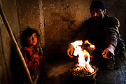 Afghanistan: Ghulam Eshan, 40 years old and one of his 7 daughters seek warmth around a charcoal fire at their makeshift home at Tamil Mill Bus site in Kabul city. ..Ghulam and his family have been living in an abandoned building, at Tamil Mill Bus site, one of dozens of Kabul Informal Settlements for the past 9 years. he says he is unable to return to Parwan, his home is destroyed, there is no prospect of employment and conflicts with tribal elders in the region forbid him from returning. He earns between 80-90 Afs (approx. US$2) per day from using his 'karachi' or wheelbarrow transporting goods and foods around the market areas...Whilst in the city he says food is sometimes brought from the hospital and sold cheaply in the market areas, he relies on this to feed his family. His wife, 35 year old Zazabour sometimes goes begging in her blue burqa to bring in extra money...Only one of their 8 children, 10 year old Ferishta attends school. The remaining children search the garbage dumps nearby for items they can take tot he recycling centre...Zazabour says almost all the clothes worn by the children were obtained from going door to door in the city begging for clothes. They have no running water or electricity in the building but rely in UNHCR for charcoal and NFI distribution...Ghulam does not see himself leaving the city, he sees even less opportunity for employment outside of Kabul and is worries about the security situation outside of the city...Tajik and Pashtun families live side by side without any major conflict at the Tamil Mill Bus site. Over 70% of the families are returnees from the period 2002-2004 who are unable to achieve sustainable reintegration in their places of origin and subsequently drifted to Kabul City in search of work...There is a nearby school which is accessible to the children but the poor economic circumstances of the many families oblige them to send their children out to work. low levels of literacy, particularly amongst the women, limi
