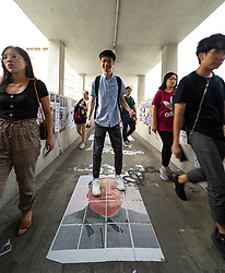 People walk over poster of Mao Zedong in Kowloon Tong. Pro democracy and anti extradition law protests slogans and posters on Lennon Wall in Hong Kong