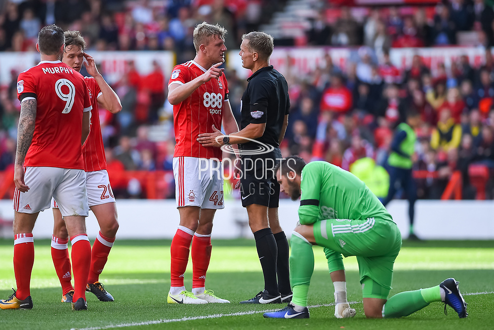 Nottingham Forest defender Joe Warrall (42) has words with referee Graham Scott after Nottingham Forest goalkeeper Jordan Smith (43) is fouled during the EFL Sky Bet Championship match between Nottingham Forest and Middlesbrough at the City Ground, Nottingham, England on 19 August 2017. Photo by Jon Hobley.