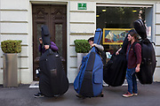 On their way to a concert that evening, musicians cary their bulky double-bass musical instruments through Levstikov street in the Slovenian capital, Ljubljana, on 27th June 2018, in Ljubljana, Slovenia.