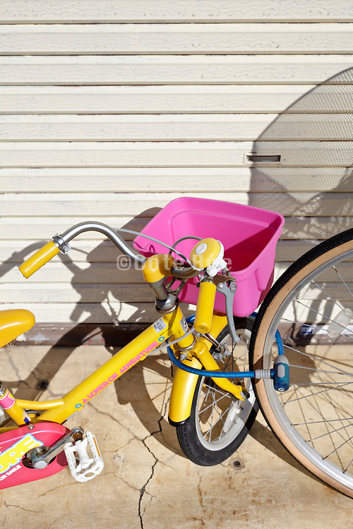 little colorful child bicycle locked to a large adult bicycle wheel