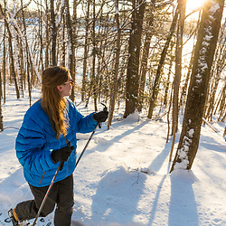 A woman snowshoeing through the forest above Indian Hill Reservoir in West Newbury, Massachusetts.
