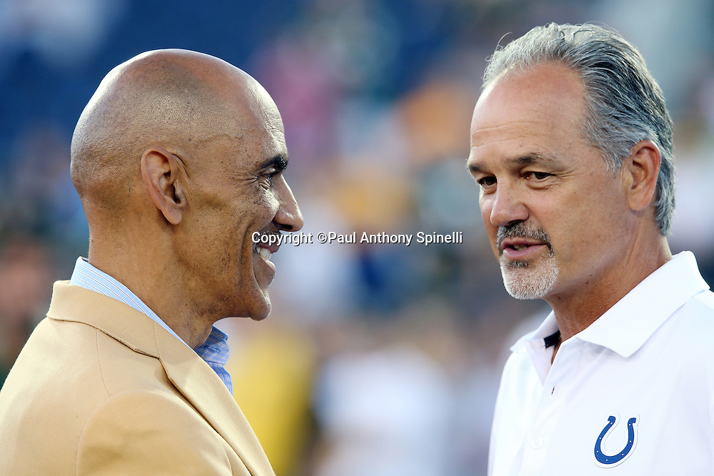 Former Indianapolis Colts head coach Tony Dungy speaks with Indianapolis Colts head coach Chuck Pagano before the 2016 NFL Pro Football Hall of Fame preseason football game against the Green Bay Packers on Sunday, Aug. 7, 2016 in Canton, Ohio. The game was canceled for player safety reasons due to the condition of the paint on the turf field. (©Paul Anthony Spinelli)