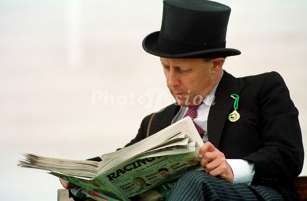 Toff reading Racing Post newspaper dressed up for the races UK