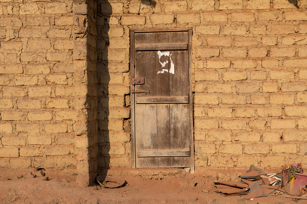 A wooden door is closed and surrounded by a mud brick wall Ganta, Liberia