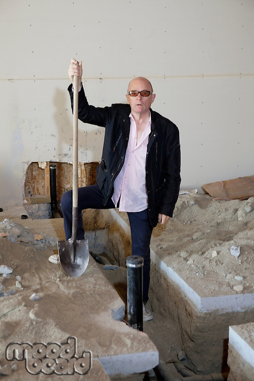 Portrait of senior owner of property standing with shovel at construction site