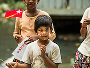 25 OCTOBER 2015 - SHWEPYITHAR, MYANMAR: A child in Shwepyithar, Myanmar, with National League for Democracy stickers on his face. Political parties are in fill campaign mode in Myanmar (Burma). National elections are scheduled for Sunday Nov. 8. The two principal parties are the National League for Democracy (NLD), the party of democracy icon and Nobel Peace Prize winner Aung San Suu Kyi, and the ruling Union Solidarity and Development Party (USDP), led by incumbent President Thein Sein. There are more than 30 parties campaigning for national and local offices.     PHOTO BY JACK KURTZ