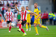 Dylan McGeouch (#8) of Sunderland AFC gets to the ball ahead of Scott Wagstaff (#7) of AFC Wimbledon during the EFL Sky Bet League 1 match between Sunderland and AFC Wimbledon at the Stadium Of Light, Sunderland, England on 24 August 2019.