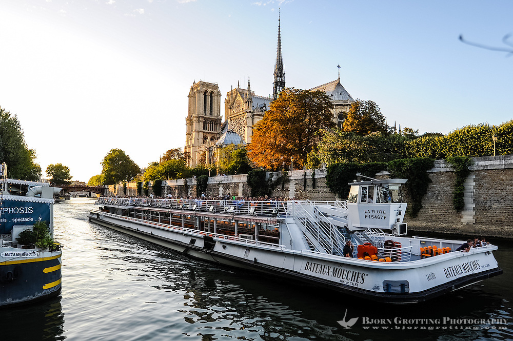 Paris, France. One of the many sightseeing boats on the river Seine passing the Notre Dame cathedral.