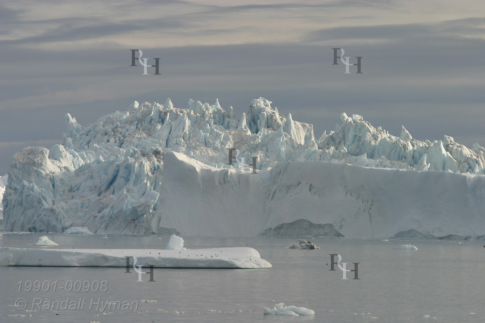 Massive icebergs loom over calm waters of Disko Bay at mouth of Ilulissat Kangerlua Icefjord, Greenland.