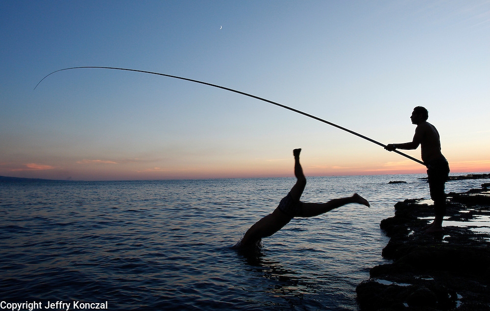 A man dives into the Mediterranean sea as another man fishes along the coast in Beirut, Lebanon.
