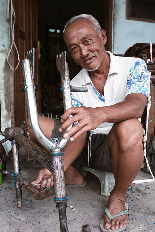 An elderly man works on fixing bikes up in Yogyakarta.