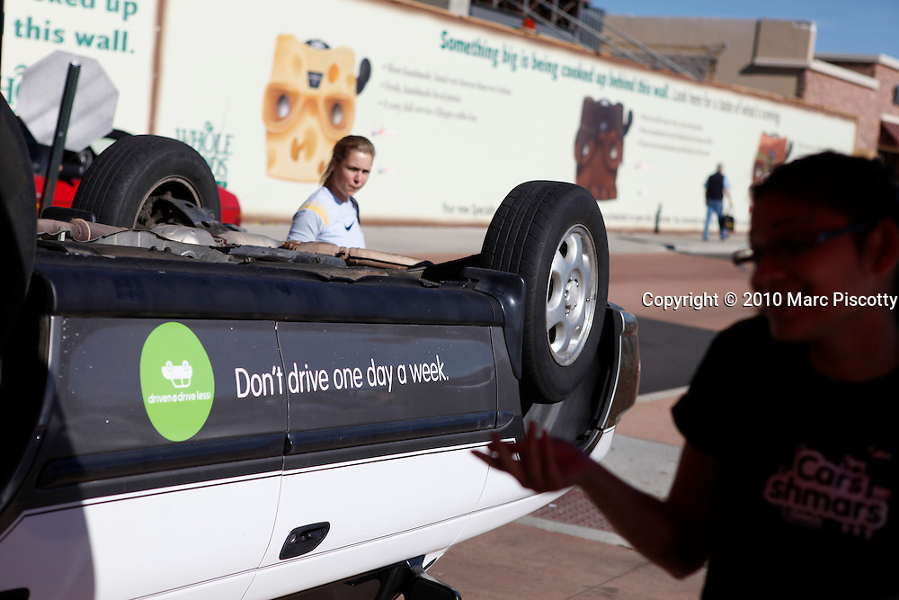 SHOT 11/6/10 12:49:44 PM - Members of Driven to Drive Less display a car turned upside down and offer free bike tunes and maintenance in front of the Whole Foods grocery store in Boulder, Co. on Saturday November 7, 2010. Driven to Drive Less is a program being undertaken by the city of Boulder, Co. that encourages participants to stimulate long term travel behavior change and to creatively demonstrate to the general public the ability of Boulder residents to live car free or car lite. Participants receive benefits and discounts at local stores for pledging to give up driving their vehicle one day a week. (Photo by Marc Piscotty / © 2010)
