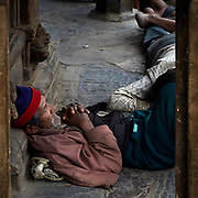 Coolies at rest against a temple front in Kathmandu, Nepal